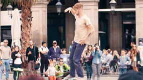 BARCELONA, SPAIN - APRIL, 16, 2017. Tightrope acrobat performing in the street. Balancing on a swaying strap. BARCELONA, SPAIN - APRIL, 16, 2017. Acrobat royalty free stock image