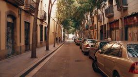 BARCELONA, SPAIN - APRIL, 15, 2017. Steadicam shot of a narrow street with parked cars. 4K clip. BARCELONA, SPAIN - APRIL, 15, 2017. Steadicam shot of a narrow stock video footage