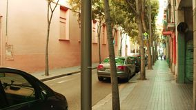 BARCELONA, SPAIN - APRIL, 15, 2017. Steadicam shallow focus shot of a narrow street with parked cars. 4K video. BARCELONA, SPAIN - APRIL, 15, 2017. Steadicam stock footage