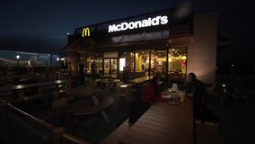 Barcelona, Spain - April 27, 2018: A young couple eating at McDonald s summer tables late in the evening. McDonalds fast stock video footage