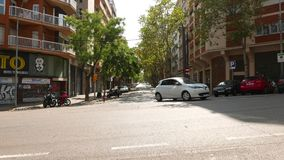 Car turning at intersection, parked cars and bikes along street. Barcelona, Spain - August, 12, 2018: Car turning at intersection, empty road, parked cars and stock video