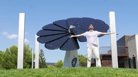 Happy Man stretched out arms, enjoy pure sun energy against solar panel stock video
