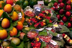 Barcelona, Spain - August 1, 2018: La Boqueria market, Stall of peach, mango and plastic boxes of berries marketplace. Barcelona, Spain - August 1, 2018: La royalty free stock photos