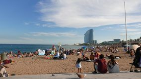 People relaxing at Barceloneta beach, W Hotel panorama, Barcelona stock video