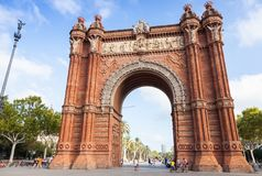 People walk near Arc de Triomf, Barcelona. Barcelona, Spain - August 26, 2014: People walk near Arc de Triomf or Arco de Triunfo in Spanish. It is a triumphal Royalty Free Stock Images