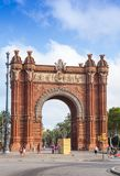 Triumphal arch in Barcelona, Spain. Barcelona, Spain - August 26, 2014: People walk near Arc de Triomf, triumphal arch in the city of Barcelona in Catalonia Royalty Free Stock Photos