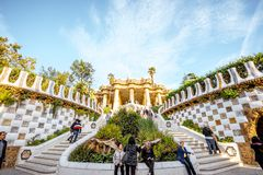 Guell park in Barcelona. BARCELONA, SPAIN - August 17, 2017: View on the Dragon stairway and terrace with tourists in Guell park, famous public park with gardens Stock Images