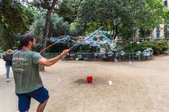 BARCELONA, SPAIN. July 6, 2017: Street artists make soap bubbles in the Plaza de Gaudi for the enjoyment of children and tourists Royalty Free Stock Images