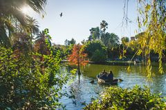 Barcelona, Spain - 24.11.2018: Beautiful day in Ciutadella Park, view of green trees and a boat with people in a small lake from. The park royalty free stock images