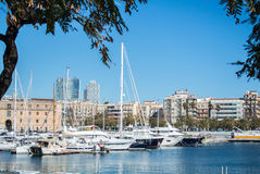BARCELONA, SPAIN - FEBRUARY 12, 2014: A view to a pier with yachts at Barcelona port. Catalonia, Spain Stock Photos