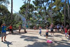 BARCELONA, SPAIN - JULY 8, 2014:  A street entertainer performs. His bubble show for a group of tourists in famous Park Guell on July 8, 2014 in Barcelona Stock Images