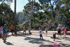 BARCELONA, SPAIN - JULY 8, 2014:  A street entertainer performs. His bubble show for a group of tourists in famous Park Guell on July 8, 2014 in Barcelona Stock Photography