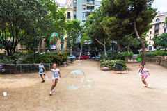 BARCELONA, SPAIN. 6 July 2017: Unidentified children play in Gaudi Square with soap bubbles made by a street artist Stock Photos