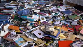 Old books on sale at a flea market on the floor.