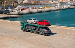 Barcelona, Spain - March 30, 2016: tow truck carry Seat and Mercedes cars in sea port. Auto export and import trade. Vehicles shipment trade. Trade and royalty free stock photos