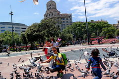 Barcelona, Spain - May 17, 2014: Placa Catalunya. tourists feeding pigeons. Royalty Free Stock Photography