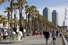 Barcelona, Spain, 03 May 2020: Two police officers on horses on the Barcelona beach promenade watching people walking and doing