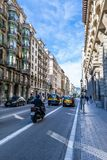 Taxi Cabs, private cars and a motorcyclist on a sunny day in the streets of Barcelona and pedestrians walking on the road. royalty free stock photos