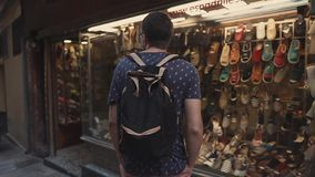 Barcelona, Spain - September 2018: Gothic Quarter in downtown of city. Adult man is examining a showcase with summer. Barcelona, Spain - September 2018: Gothic stock video