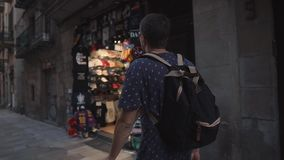 Barcelona, Spain - September 2018: Historical district of city Gothic Quarter. Tourist man is viewing small gift shops. Barcelona, Spain - September 2018 stock footage