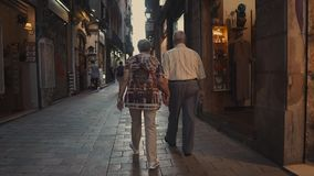 Barcelona, Spain - September 2018: Pedestrian street in Gothic Quarter. Senior pair is walking together along souvenir. Barcelona, Spain - September 2018 stock video