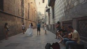 Barcelona, Spain - September 2018: Picturesque small lane in the Gothic Quarter. Pair of honeymooners are dancing on. Barcelona, Spain - September 2018 stock video