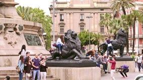 BARCELONA SPANIEN - APRIL, 15, 2017 Turister som gör foto nära Columbus Monument lejon video 4K arkivfilmer