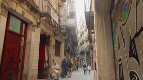 BARCELONA SPANIEN - CIRCA NOVEMBER 2017: Folk som rusar i smal gata av gotiskt område lager videofilmer