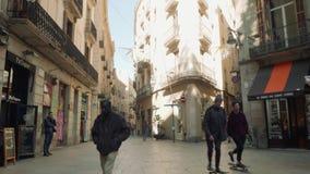 BARCELONA SPANIEN - CIRCA NOVEMBER 2017: Folket går i gata nära diversehandel och caffes arkivfilmer