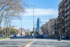 BARCELONA SPANIEN - FEBRUARI 12, 2014: En sikt av en gata av Barcelona med bilar, folk och moderna byggnader Fotografering för Bildbyråer