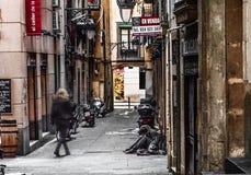 Barcelona Spanien, i stadens centrum gränd, smal gata, kvinna som sitter på jordningen royaltyfria bilder