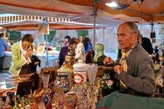 Barcelona Spanien - Maj 17, 2014: Säljaren av souvenir Turister beskådar godset Arkivfoto