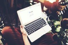 Barcelona Spanien - 01 02 2016: Man registreringsGoogle sida Den generiska designbärbara datorn är på hans knä Social nätverksskä Royaltyfria Foton