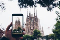 BARCELONA SPANIEN - SEPT 16, 2017 - turist- tagande foto av den berömda kyrkan av den heliga familjen med den smarta telefonen fö Royaltyfri Foto
