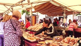 BARCELONA, SPANJE - APRIL, 15, 2017 Vrouwelijke gebakjeverkoper en klant bij lokale voedselmarkt royalty-vrije stock fotografie