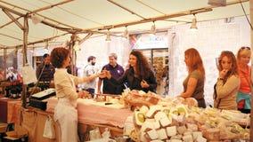BARCELONA, SPANJE - APRIL, 15, 2017 Vrouwelijke kaasverkoper en kopers bij lokale markt stock afbeeldingen