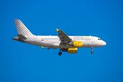 BARCELONA, SPANJE - AUGUSTUS 20, 2016: Het vliegtuig Vueling vliegt over Barcelona Blauwe hemel Stock Afbeeldingen