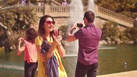 BARCELONE, ESPAGNE - AVRIL, 16, 2017 Jeune femme faisant des selfies avec un téléphone portable près de la fontaine de parc vidéo clips vidéos