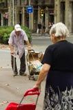 Barcelone, Espagne, le 16 août 2016 : Le vieil homme et la femme avec le chariot marchent sur la rue Photographie stock libre de droits