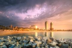 Barceloneta Beach in Barcelona at sunrise, Spain. Barceloneta Beach in Barcelona with rocky coastline and colorful sky at sunrise, Spain Stock Image
