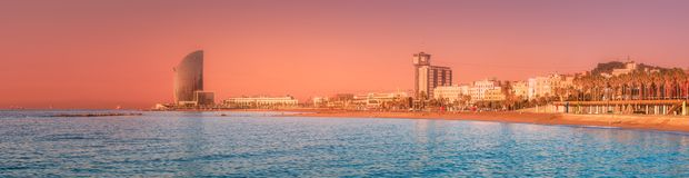 Barceloneta Beach in Barcelona at sunrise, Spain. Barceloneta Beach in Barcelona with rocky coastline and colorful sky during pink sunrise, Spain royalty free stock images
