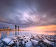 Barceloneta Beach in Barcelona at sunrise, Spain. Barceloneta Beach in Barcelona with rocky coastline and colorful sky during violet sunrise, Spain Stock Photos