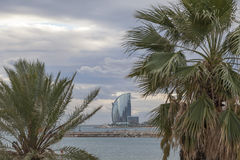 Barceloneta beach, Hotel W or Hotel Vela, by architect Ricard Bofill between palm tree. Barcelona. Royalty Free Stock Images