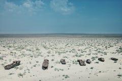 Barche abbandonate che arrugginiscono via nella sabbia al porto marittimo una volta di fioritura Fotografie Stock