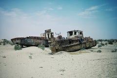 Barche abbandonate che arrugginiscono via nella sabbia al porto marittimo una volta di fioritura Immagine Stock