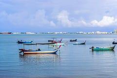 Barche al pilastro in oceano con cielo blu Fotografia Stock