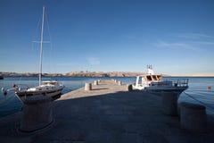 Barche attraccate ad un pilastro alla costa adriatica in Croazia fotografia stock