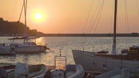 Barche attraccate con l'attrezzatura di pesca che galleggia al bacino, vista sul mare romantica, tramonto archivi video