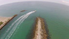 Barche che lasciano entrata costiera stock footage
