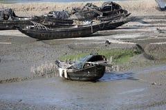 Barche dei pescatori incagliati nel fango a bassa marea sulla città d'inscatolamento vicina di Malta del fiume, India Immagini Stock